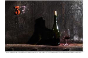 Vinflaska, glas och gammalt ekfat
